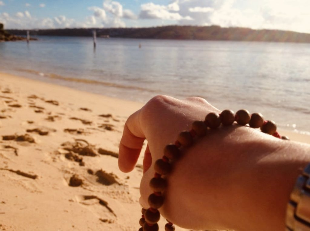 Imperfect Parenting Podcast photo of Jana Parundevi Huberova hand with meditation beads pointing to the beach as this meditation for parents is about the beach